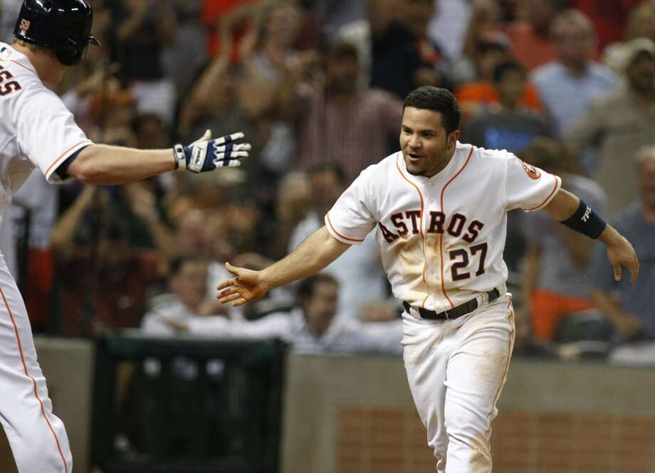 Astros second baseman Jose Altuve is congratulated by L.J. Hoes after scoring in the sixth inning. Photo: Johnny Hanson, Houston Chronicle