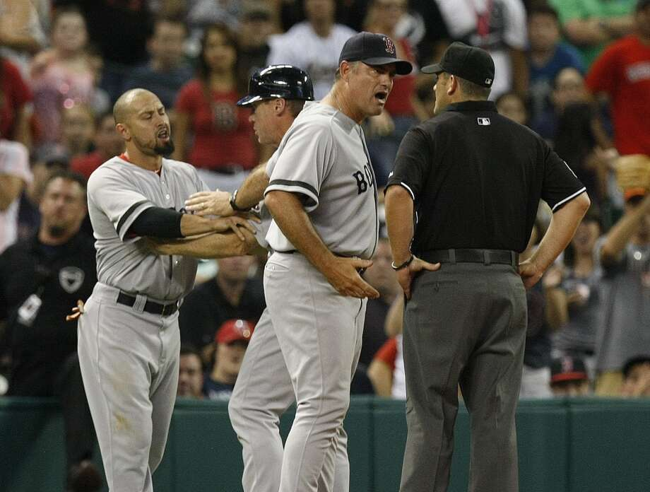 Red Sox third base coach Brian Butterfield holds back Red Sox right fielder Shane Victorino as Red Sox manager John Farrell argues with umpire Brian Knight about a called strike. Victorino was ejected. Photo: Johnny Hanson, Houston Chronicle
