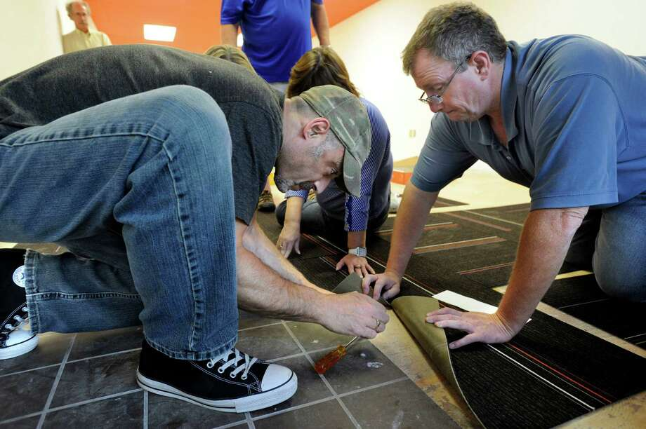 Paul Minigiello, left and, Kevin Rabito, both of Danbury, Conn., lay carpet tiles on the floor of the new home of the Cultural Alliance of Western Connecticut on Main Street in Danbury, Wednesday, August 7, 2013. Photo: Carol Kaliff / The News-Times