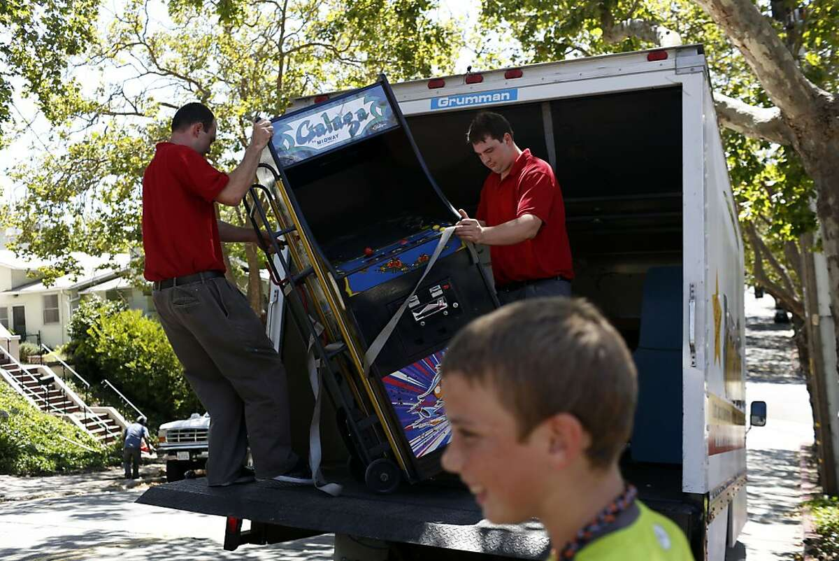 Seth Peterson, left, and Tim Peterson, right, pull out an arcade game on a delivery of arcade games for All You Can Arcade while Judge Williams watches in Oakland, Calif. on July 24, 2013.