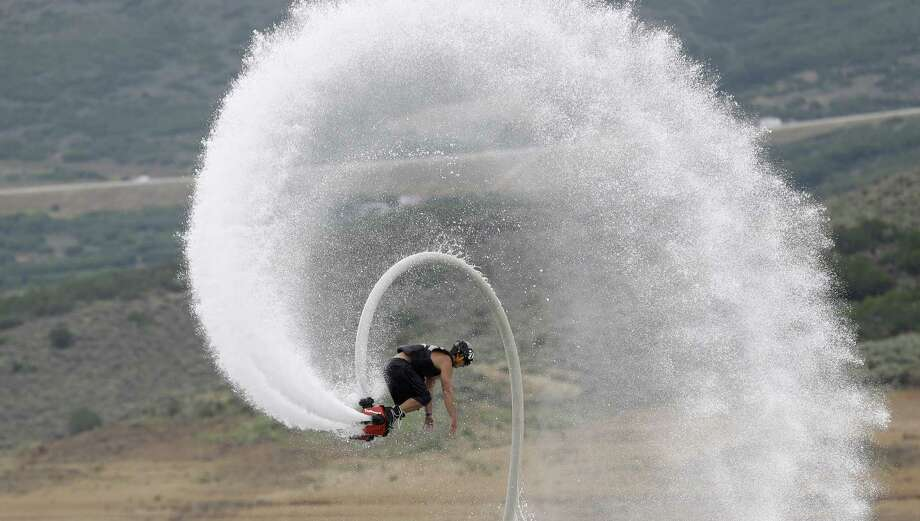 This July 24, 2013, photo, Rocky Mountain Flyboard instructor Chase Shaw flips with his flyboard, on the Jordanelle Reservoir, at Jordanelle State Park, Utah. The Flyboard, which looks like a small snowboard attached to a hose, can propel you 45 feet in the air using water pumped from a personal watercraft like a Jet Ski to the base of the board. New devices that pump water fast enough to make people defy gravity are drawing thrill-seekers eager to try the next new watersport, but Hawaii fishermen, scientists and state officials are questioning their safety and how they may affect fish, coral and other fragile natural resources in the islands. (AP Photo/Rick Bowmer) ORG XMIT: UTRB102 Photo: Rick Bowmer, AP / AP