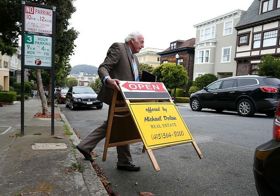 Real estate agent Maurice Dolan places an open house sign in front of a home for sale on July 30, 2013 in San Francisco, California.  Photo: Justin Sullivan, Getty Images