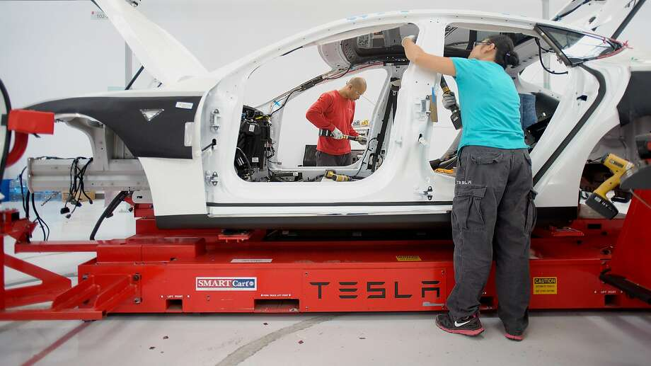 Workers add seat belts to a Telsa Motor Inc. Model S sedan at the company's assembly plant in Fremont, California, U.S., on Wednesday, July 10, 2013. Tesla is building Model S electric sedans faster than its initial 400-a-week goal as demand and the company's production skills increase, Chief Executive Officer Elon Musk said. Photographer: Noah Berger/Bloomberg Photo: Noah Berger, Bloomberg