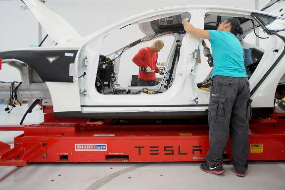 Workers add seat belts to a Telsa Motor Inc. Model S sedan at the company's assembly plant in Fremont, California, U.S., on Wednesday, July 10, 2013. Tesla is building Model S electric sedans faster than its initial 400-a-week goal as demand and the company's production skills increase, Chief Executive Officer Elon Musk said. Photographer: Noah Berger/Bloomberg