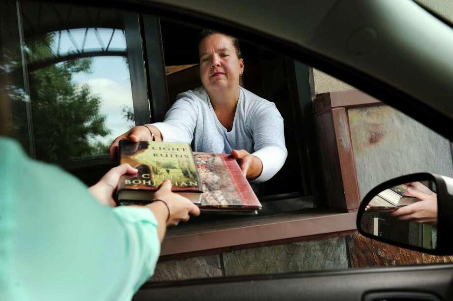 Dawn Geurds, head of circulation, hands off books via the drive thru window on Wednesday, Aug. 7, 2013, at East Greenbush Community Library in East Greenbush, N.Y. (Cindy Schultz / Times Union) Photo: Cindy Schultz / 00023439A
