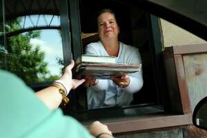 Dawn Geurds, head of circulation, hands off books via the drive thru window on Wednesday, Aug. 7, 2013, at East Greenbush Community Library in East Greenbush, N.Y. (Cindy Schultz / Times Union)