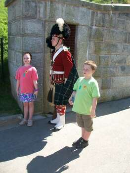"Taken in July in Halifax, Nova Scotia.  I took all four of my children to visit an excellant living history demonstration that Parks Canada maintains at a 19th century fort.  This involves some 50 college students hired to present the 78th Highlanders as they would have looked in garrison at the fort in 1869.  The children all enjoyed the morning, but these two (Michael and Olivia, both age 9)insisted on going back.  They couldn't freeze for as long as the young man in the kilt, but they ""guarded the post"" quite sharply for a good while.