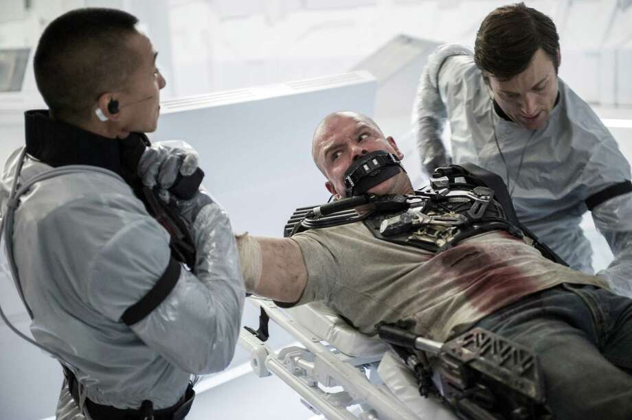 """This film publicity image released by TriStar, Columbia Pictures-Sony shows Matt Damon, center, in a scene from """"Elysium."""" (AP Photo/TriStar, Columbia Pictures - Sony, Kimberley French) ORG XMIT: NYET848 Photo: Kimberley French / TriStar, Columbia Pictures-Sony"""