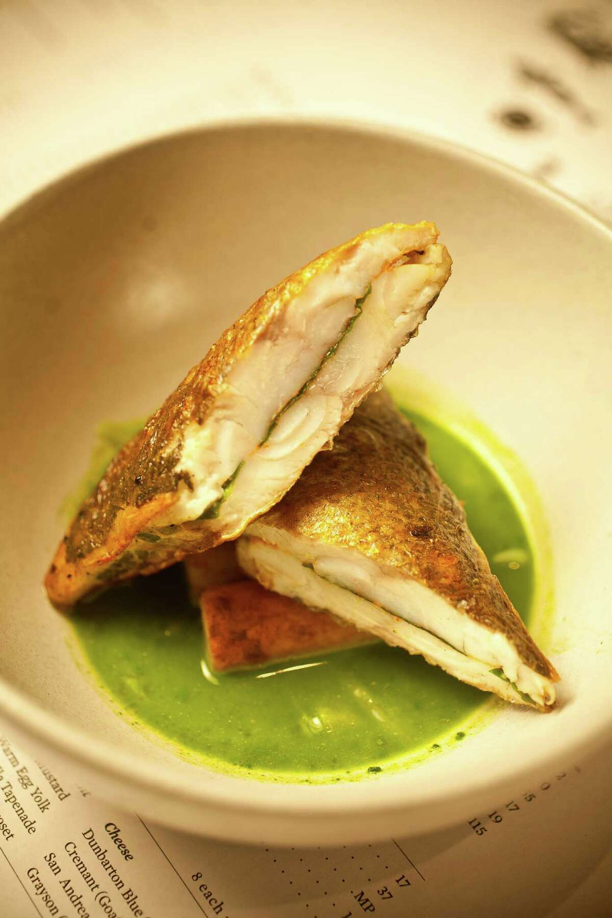 The Pass & Provisions' branzino fillets sandwiching lovage on a mussel/parsley/ginger soup with marrow browned potatoes, Tuesday, Sept. 11, 2012, in Houston. ( Nick de la Torre / Houston Chronicle )