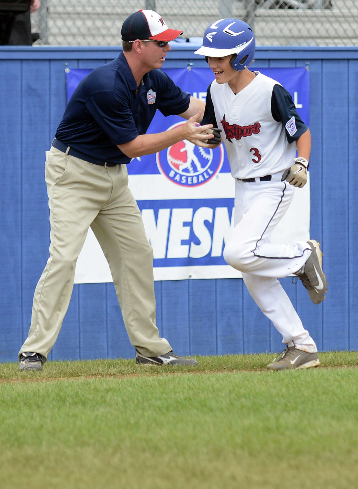 Westport coach Tim Rogers congratulates player Max Popken as he runs home after hitting a home run in the first inning of the Little League Baseball Eastern Regional Tournament game against Sacro/Maremont, of Maine, at Breen Field in Bristol, Conn. Thursday, August 8, 2013.