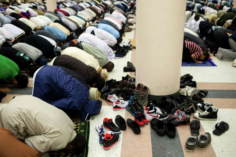 Shoes litter the exhibition hall during a Eid-ul-Fitr community prayer service Thursday , August 8, 2013, at the Seattle Center in Seattle. The holiday celebrated by Muslims worldwide marks the end of Ramadan, the Islamic holy month of fasting. Photo: JORDAN STEAD, SEATTLEPI.COM / SEATTLEPI.COM