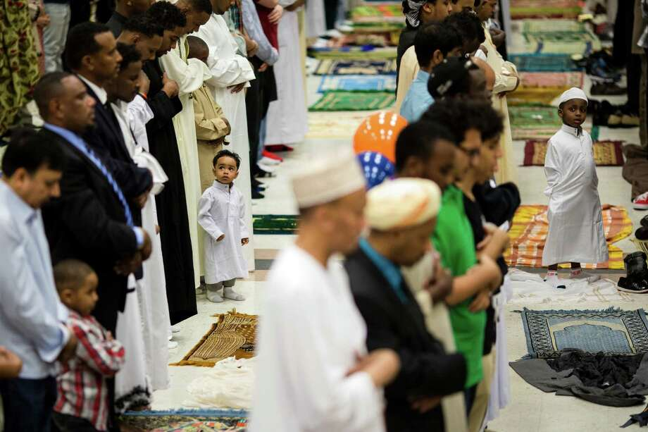 Two boys look to their family members during a Eid-ul-Fitr community prayer service Thursday , August 8, 2013, at the Seattle Center in Seattle. The holiday celebrated by Muslims worldwide marks the end of Ramadan, the Islamic holy month of fasting. Photo: JORDAN STEAD, SEATTLEPI.COM / SEATTLEPI.COM