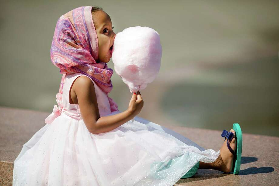 Harlem Adams, 4, enjoys a cloud of cotton candy following a Eid-ul-Fitr community prayer service Thursday , August 8, 2013, at the Seattle Center in Seattle. The holiday celebrated by Muslims worldwide marks the end of Ramadan, the Islamic holy month of fasting. Photo: JORDAN STEAD, SEATTLEPI.COM / SEATTLEPI.COM