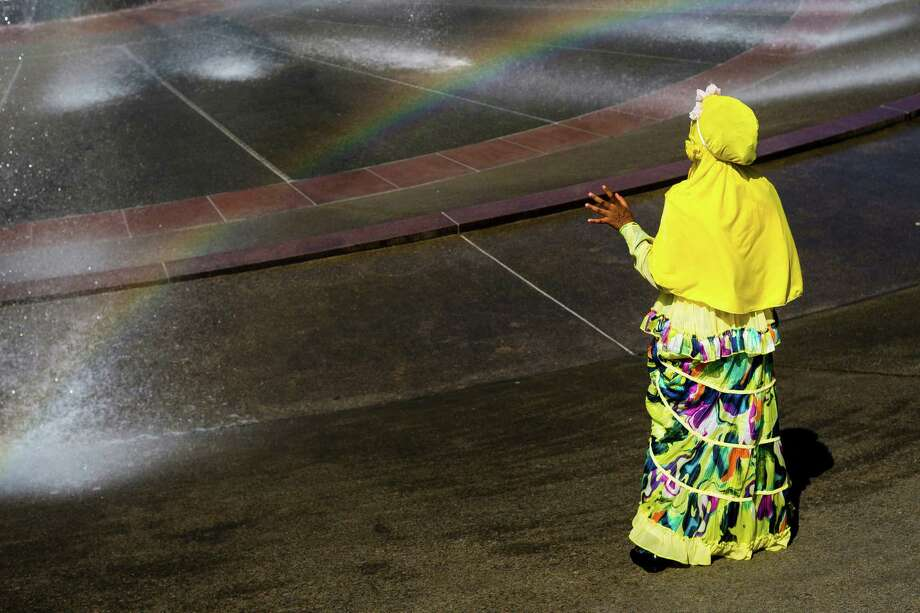 Symeyya Osman watches a rainbow form in the mist of the International Fountain following a Eid-ul-Fitr community prayer service Thursday , August 8, 2013, at the Seattle Center in Seattle. The holiday celebrated by Muslims worldwide marks the end of Ramadan, the Islamic holy month of fasting. Photo: JORDAN STEAD, SEATTLEPI.COM / SEATTLEPI.COM