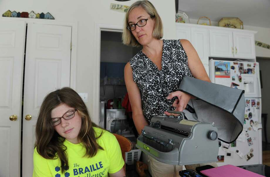 Kelly Cusack, a 12-year old girl who's completely blind, works with her mother Jennifer Cusack, right, at their home Friday, July 19, 2013, in Glenmont, N.Y. Cusack placed first in the National Braille Challenge in Los Angeles a month ago. (Michael P. Farrell/Times Union) Photo: Michael P. Farrell / 10023106A