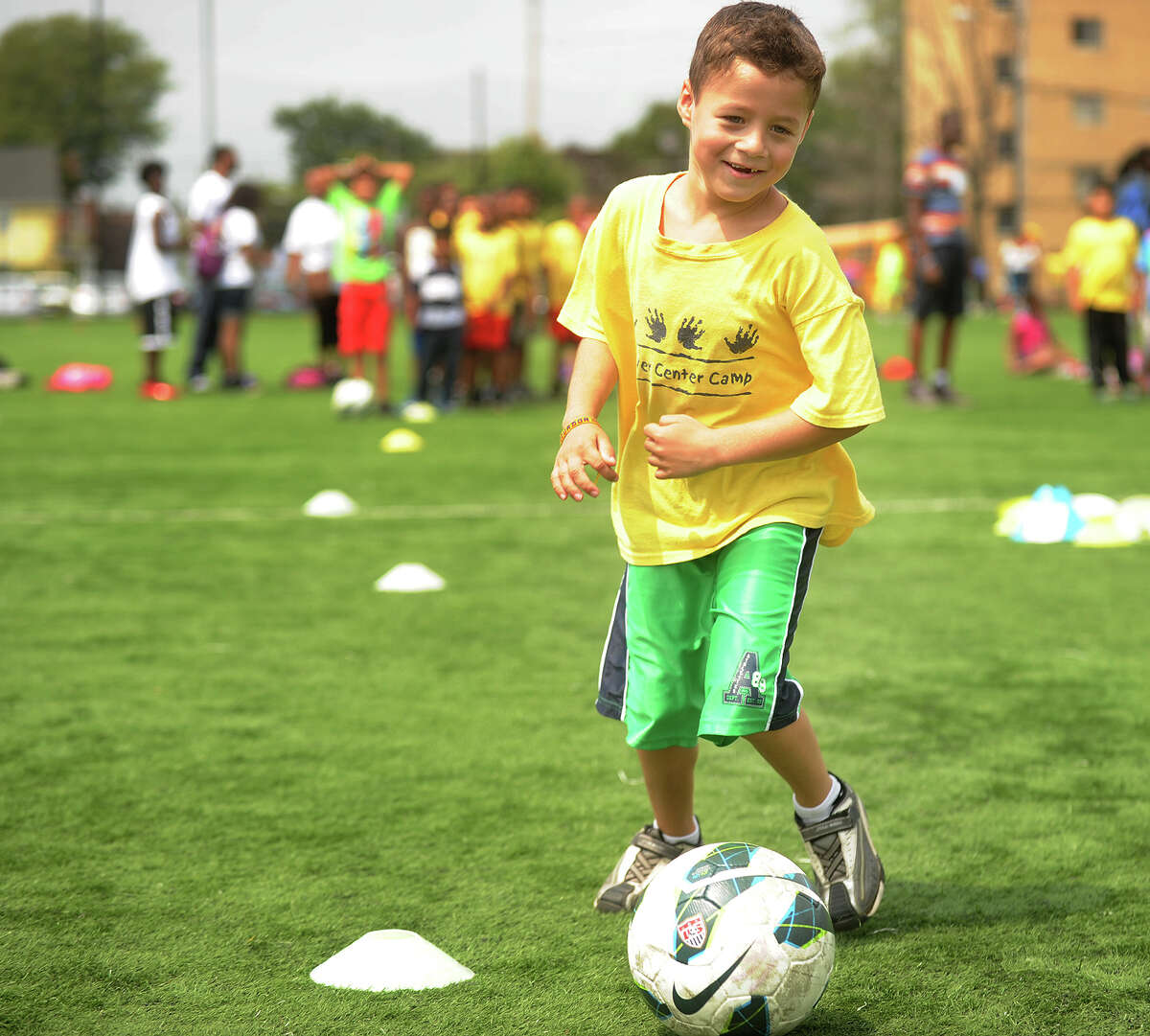 Carver Center Camp camper Eddie Vera, 8, of Norwalk, participates in a soccer drill during the Third Annual Chelsea Cohen Fitness Academy Jamboree at the University of Bridgeport on Thursday, August 8, 2013.