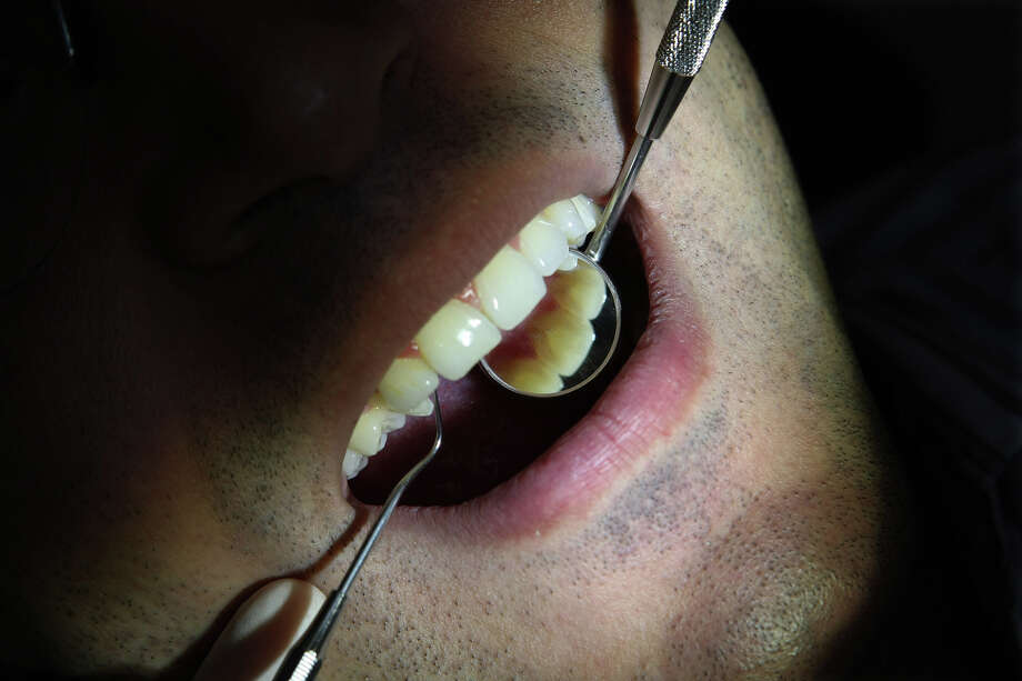 GUM DISEASE: The latest research deepens understanding of the link between dental health and disease, leading scientists to think that something as simple as treating gum disease could limit damage from some of the world s most widespread and costly illnesses. Here, a patient has his teeth examined at a London clinic in 2008. (MUST CREDIT: Bloomberg News photo by Suzanne Plunkett). Photo: Suzanne Plunkett, Bloomberg News / BLOOMBERG