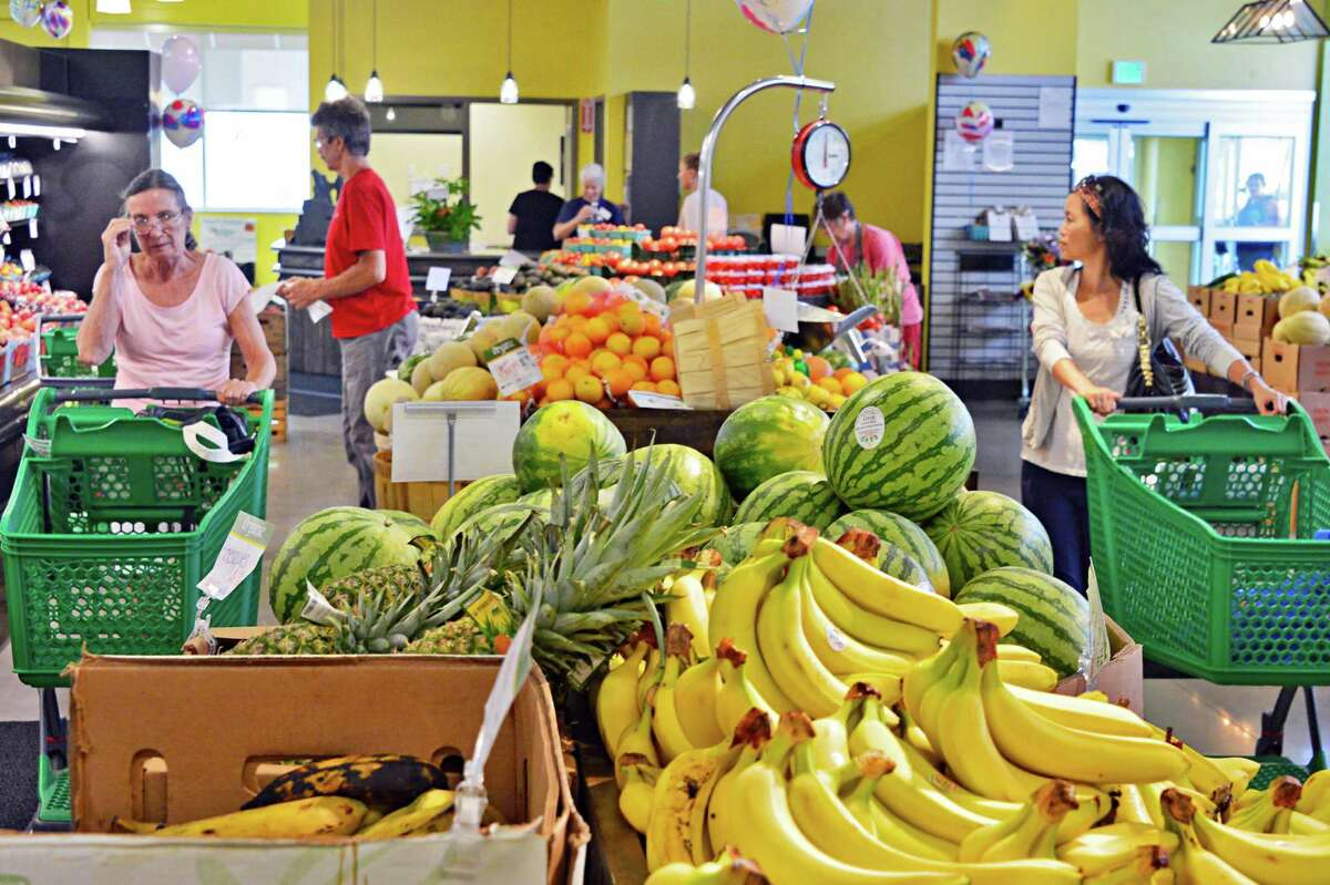 Shoppers look over the produce at Honest Weight Co-Op's new store on Watervliet Ave. Thursday, Aug. 8, 2013, in Albany, NY. (John Carl D'Annibale / Times Union)