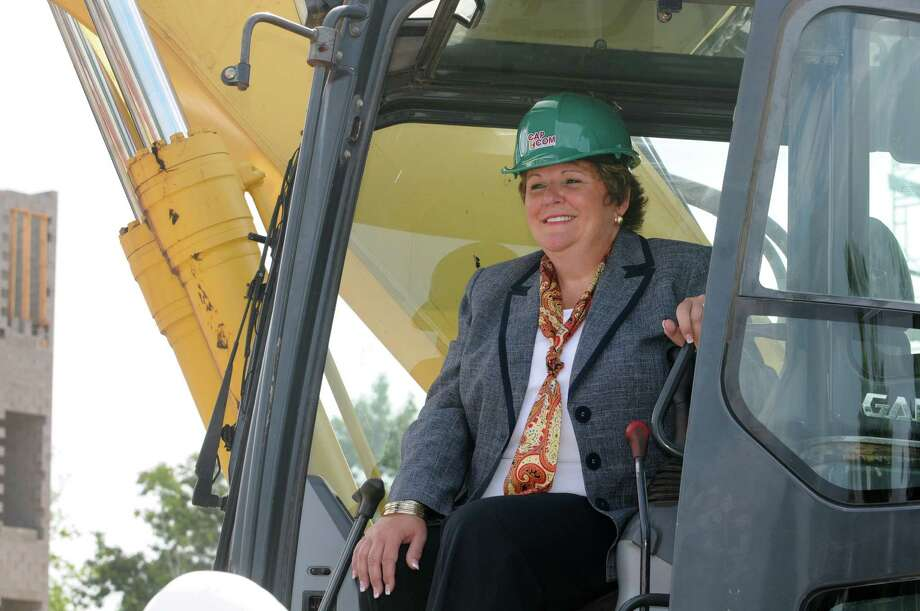 Cap Com CEO Paula Stopera takes a seat in an excavator during a groundbreaking Thursday morning, Aug. 8, 2013, for a new Cap Com Financial Center in Colonie, N.Y. (Lori Van Buren / Times Union) Photo: Lori Van Buren / 00023456A