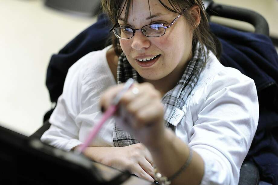 Jennifer Lortie, whose cerebral palsy limits arm and leg use, works on an iPad in her Willimantic, Conn., office. Photo: Jessica Hill, Associated Press