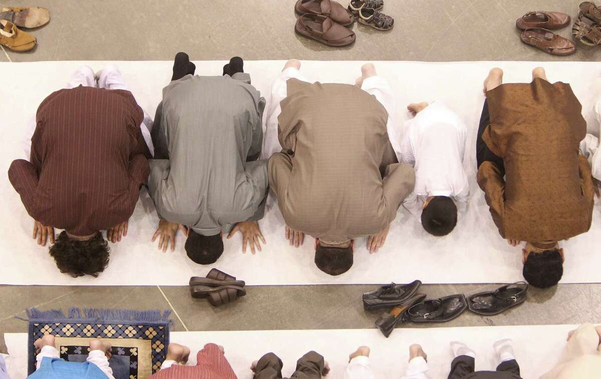 Men pray during the Eid ul Fitr prayer service and celebration at Reliant on Thursday, Aug. 8, 2013, in Houston.