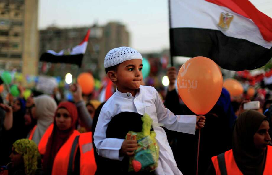 """An Egyptian boy holds a balloon has Arabic writing which reads """" No for the coup,"""" as supporters of Egypt's ousted President Mohammed Morsi celebrate the first day of Eid al-Fitr feast, marking the end of the Muslim holy fasting month of Ramadan that is traditionally celebrated with special cookies, presents and new clothes outside Rabaah al-Adawiya mosque, where protesters have installed a camp and hold daily rallies at Nasr City in Cairo, Egypt, Wednesday, Aug. 8, 2013. This year's holiday of Eid al-Fitr is overshadowed by the deep divisions in Egypt, with the interim government planning to celebrate the festival with outdoor prayers in town center squares and Morsi's supporters marking the holiday with their own protest gatherings, including the two major sit-ins by the Islamists in Cairo. (AP Photo/Khalil Hamra) ORG XMIT: KH102 Photo: Khalil Hamra / AP"""