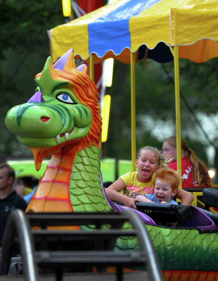 Madison Jankauskas, 10, of Ansonia, and her brother Ethan, 3, ride the kiddie rollar coaster during Holy Rosary Parish's Festa 2013, which is the parish's 46th Annual Italian Festival in Ansonia, Conn. on Thursday August 8, 2013. The annual festival opens on Thursday Aug 8 and runs through Saturday August 10 from 5-10 p.m. Photo: Christian Abraham / Connecticut Post