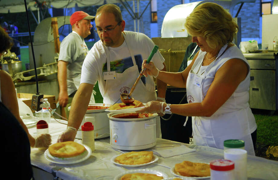 Volunteers Neil Torres, left, and Carol Pluchino get pizzas ready during Holy Rosary Parish's Festa 2013, which is the parish's 46th Annual Italian Festival in Ansonia, Conn. on Thursday August 8, 2013. The annual festival opens on Thursday Aug 8 and runs through Saturday August 10 from 5-10 p.m. Photo: Christian Abraham / Connecticut Post