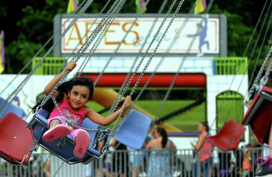 Tatiana Frouge, 6, of Ansonia, rides on the swings during Holy Rosary Parish's Festa 2013, which is the parish's 46th Annual Italian Festival in Ansonia, Conn. on Thursday August 8, 2013. The annual festival opens on Thursday Aug 8 and runs through Saturday August 10 from 5-10 p.m. Photo: Christian Abraham / Connecticut Post