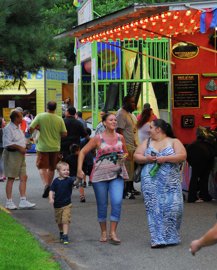Deanna Dobbins, of Derby, walks with her son Tristyn Lapke, 4, and sister Amber Sapiente, right, during Holy Rosary Parish's Festa 2013, which is the parish's 46th Annual Italian Festival in Ansonia, Conn. on Thursday August 8, 2013. The annual festival opens on Thursday Aug 8 and runs through Saturday August 10 from 5-10 p.m. Photo: Christian Abraham / Connecticut Post
