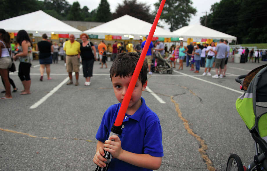 Daniel Dubinia, of Ansonia, plays with his light sabre during Holy Rosary Parish's Festa 2013, which is the parish's 46th Annual Italian Festival in Ansonia, Conn. on Thursday August 8, 2013. The annual festival opens on Thursday Aug 8 and runs through Saturday August 10 from 5-10 p.m. Photo: Christian Abraham / Connecticut Post