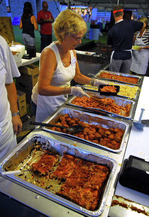Volunteer Laura Badamo get pastas for a customer during Holy Rosary Parish's Festa 2013, which is the parish's 46th Annual Italian Festival in Ansonia, Conn. on Thursday August 8, 2013. The annual festival opens on Thursday Aug 8 and runs through Saturday August 10 from 5-10 p.m. Photo: Christian Abraham / Connecticut Post