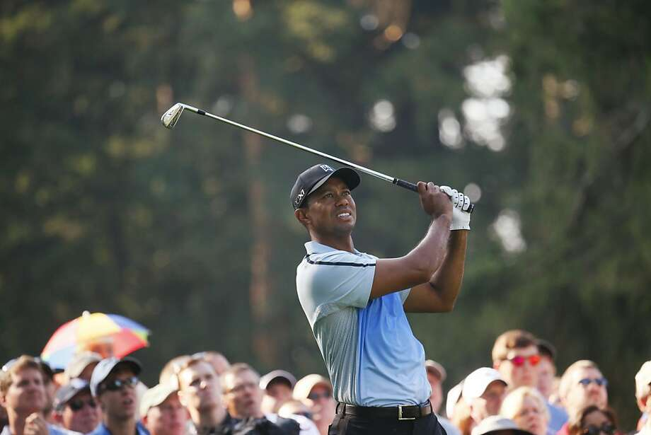 Tiger Woods watches his drive on the 11th hole at Oak Hill Country Club. He ended the opening round at 1-over-par 71. Photo: Derek Gee, Associated Press