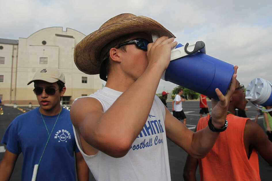 "MacArthur High School band member Brock Pugh (center) hydrates during practice in the school's parking lot Wednesday August 7, 2013. The National Weather Service has issued a heat advisory for the San Antonio area with heat indices of 105-110 degrees east of I-35. ""The kids are doing a great job of working hard and staying hydrated,"" said MacArthur assistant band director Mason Daffinee."