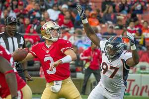 49ers quarterback Scott Tolzien is pressured by Denver's Malik Jackson at Candlestick Park in San Francisco, Calif., on Aug. 8, 2013. Tolzien is hoping to extend his career after being drafted by the Birmingham Iron in the new Alliance of American Football League.