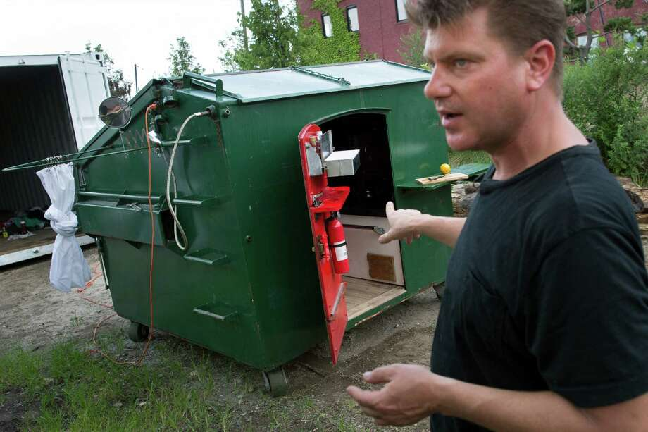 """Gregory Kloehn describes his """"dumpster home"""" to a reporter, Thursday, Aug. 8, 2013,  in the Red Hook neighborhood of New York's Brooklyn borough. The artist purchased a new dumpster and retrofitted it to be his dwelling when he stays New York City, loading it with steel appliances, an outside shower, a barbecue, a toilet and a padded area where he can lie down. (AP Photo/John Minchillo) ORG XMIT: NYJM103 Photo: John Minchillo / FR170537 AP"""
