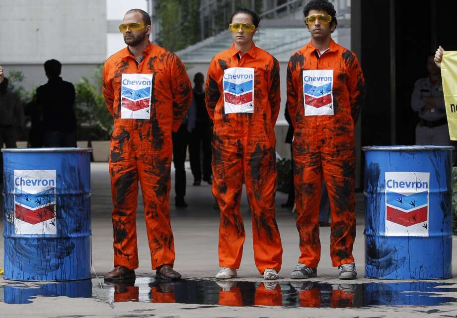 Greenpeace activists use simulated oil to protest an oil spill in an offshore field operated by Chevron Corp, outside Chevron's offices in Rio de Janeiro, Brazil, Friday Nov. 18, 2011. Photo: Silvia Izquierdo, Associated Press