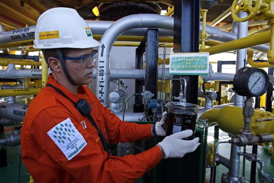 """A Petrobras worker removes the first oil extracted under a thick layer of salt beneath the ocean floor onSept. 2, 2008 on the P-34 Petrobras' platform, 75 miles east of Vitoria, Brazil. An enormous offshore field in territorial waters, then the biggest oil discovery in the Western Hemisphere in 30 years, had Brazilians saying, """"Drill, baby, drill,"""" while environmentalists worried the forward-thinking nation will take a big leap backward to focus on crude. Photo: Eraldo Peres, AP"""