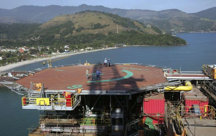 "Petrobras workers walk on platform 51 ""Majuro"" in Angra dos Reis, Brazil on Aug. 21, 2008. An enormous offshore field in territorial waters, then the biggest oil discovery in the Western Hemisphere in 30 years, had Brazilians saying, ""Drill, baby, drill,"" while environmentalists worried the forward-thinking nation will take a big leap backward to focus on crude. Photo: Ricardo Moraes, AP"