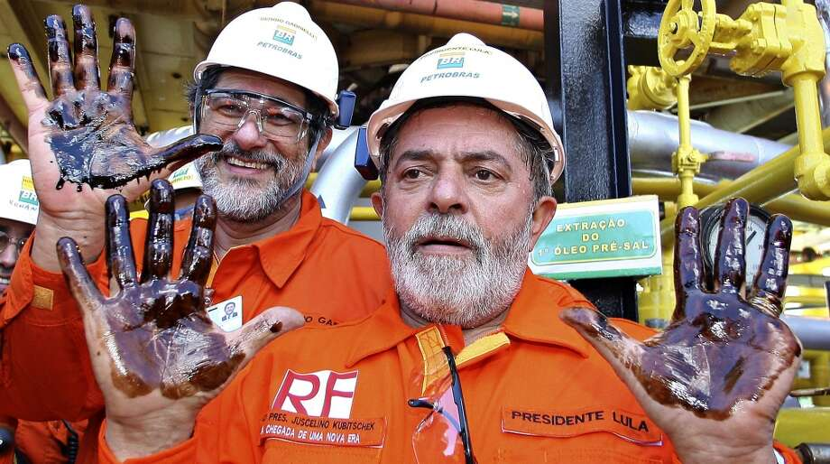 Brazil's then-President Luiz Inacio Lula da Silva, right, and Petroleo Brasileiro SA then-president, Sergio Gabrielli, show their hands covered with oil during a visit to the P-34 offshore platform, 120 kms (75 miles) east of Vitoria in the Atlantic ocean, Brazil, on Sept. 2, 2008. Photo: Ricardo Stuckert, AP