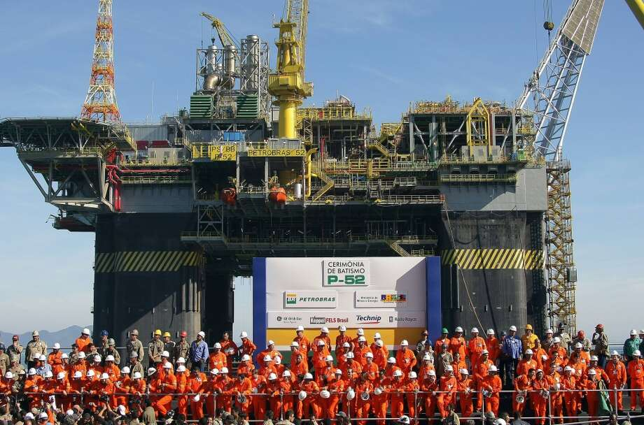 Petrobras workers pose in front of the P-52 oil platform during its launching ceremony in June 2007 in Angra dos Reis, 300km south from Rio de Janeiro, Brazil.  Brazil had discovered a new offshore oil field that professed to be the third biggest field in the world. The find, located off the southwest coast, was calculated to hold 33 billion barrels of oil. Photo: ANTONIO SCORZA, AFP/Getty Images