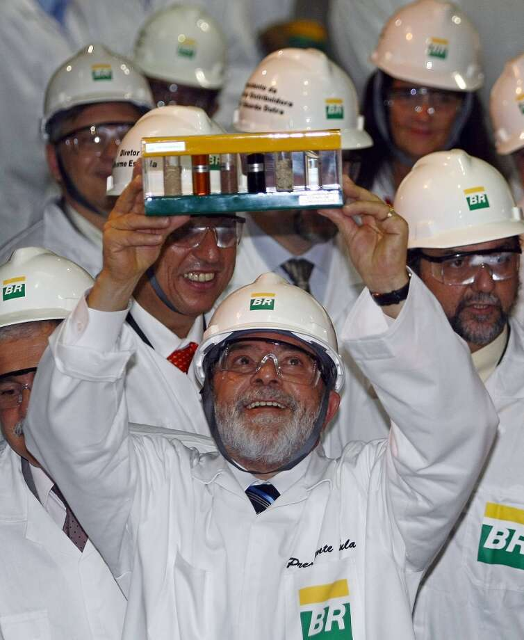 Brazil's then-president Luiz Inacio Lula da Silva holds samples of biofuel produced from sugar cane bagasse, during a visit to the Petrobras Development and Rersearch Centre in October 2007, in Rio de Janeiro. Photo: VANDERLEI ALMEIDA, AFP/Getty Images