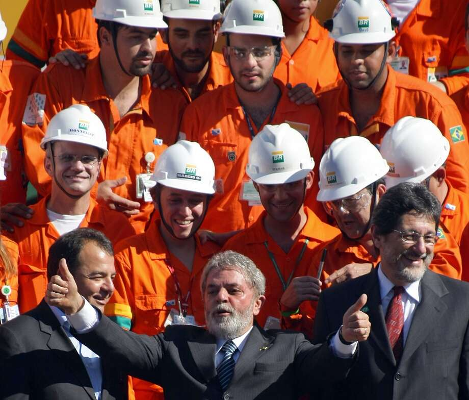 Then-Brazilian President Luiz Inacio Lula da Silva (C) congratulates Petrobras technicians and engineers (in orange coveralls) beside then-Petrobras president Sergio Gabrielli (R) and Rio de Janeiro's governor Sergio Cabral, during the launching of the P-52 oil platform in June 2007 in Angra dos Reis, 300km south from Rio de Janeiro, Brazil. Brazil had discovered a new offshore oil field that professed to be the third biggest field in the world. The find, located off the southwest coast, was calculated to hold 33 billion barrels of oil. Photo: ANTONIO SCORZA, AFP/Getty Images