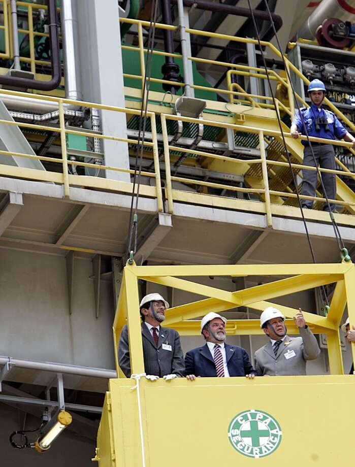 Brazil's then-President Luiz Inacio Lula da Silva (C) listens Brazilian Energy Minister Silas Rondeau (R) as Brazilian oil company Petrobras President Jose Sergio Gabrielli (L) looks on during the a launching ceremony for the P-50 offshore platform in Niteroi near Rio de Janeiro November 23, 2005. Photo: SERGIO MORAES, REUTERS