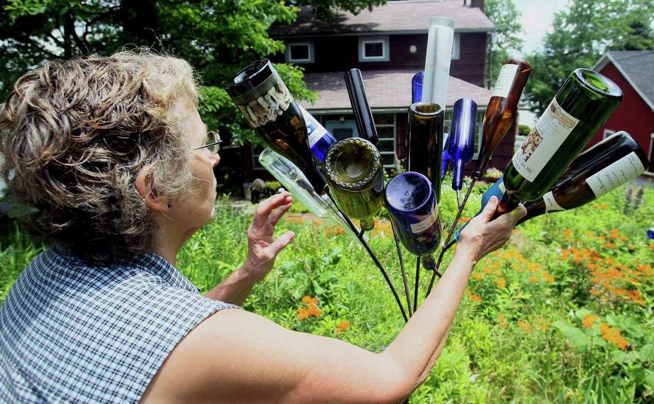 Deidre Betancourt of Ohio tends her bottle tree, a Southern tradition that's gaining popularity across the nation. Photo: Photos By Mike Cardew / Akron Beacon Journal