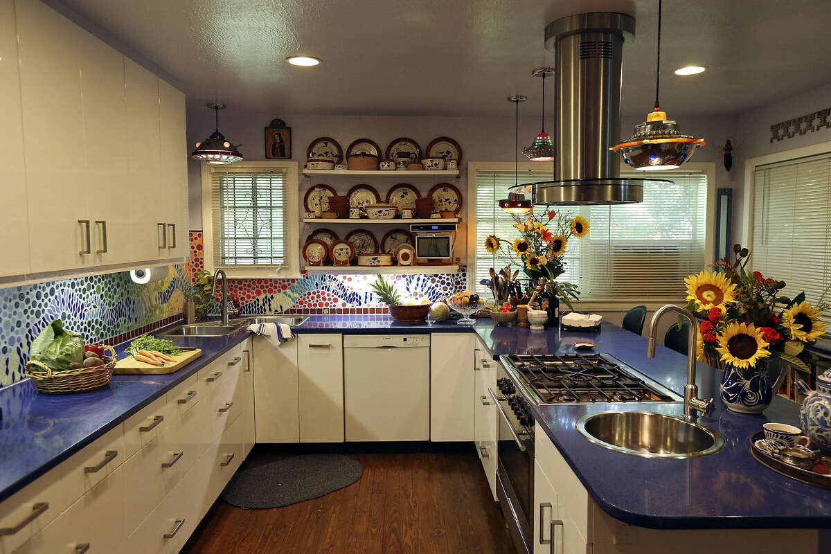 Mosaic tile backsplash and UFO-style lighting act as jewelry to the blue counters and white cabinetry of the Lanes' kitchen.