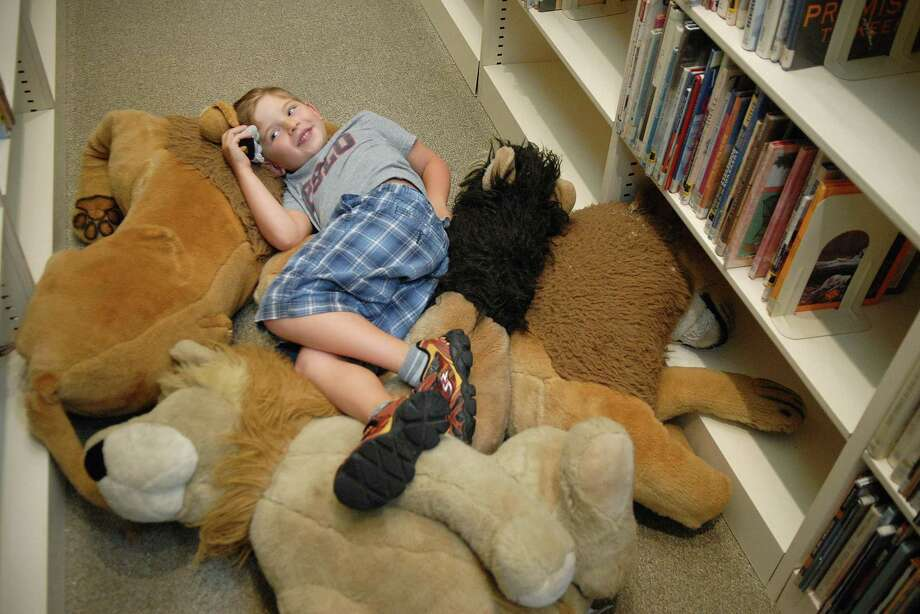 Andrew Tweeddle (6) enjoys a rest on some stuffed lions at the Perrot Memorial library in Old Greenwich on Friday August 9, 2013. Photo: Dru Nadler / Stamford Advocate Freelance