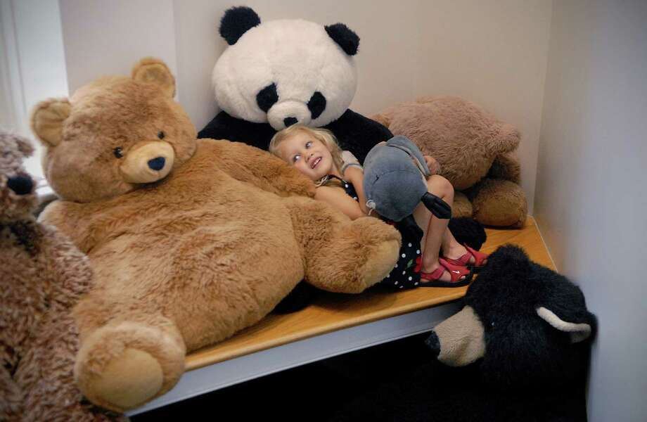 Pollyanna Seidel (3) snuggles in with the giant stuffed bears on the landing of the children's section of the Perrot Memorial library in Old Greenwich on Friday August 9, 2013. Photo: Dru Nadler / Stamford Advocate Freelance
