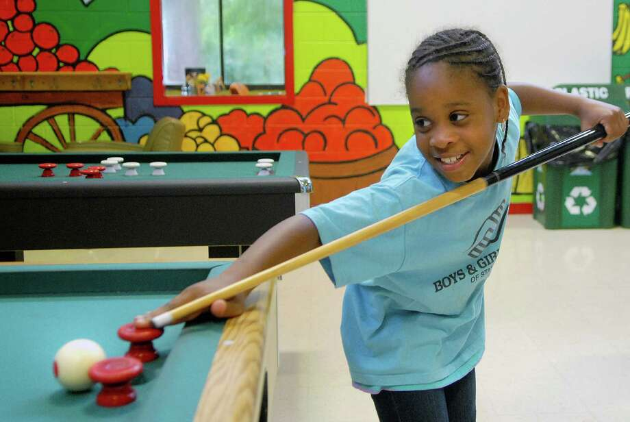 Tiffany Cadet (9) wins her 10th game in a row of bumper pool at the Boys and Girls Club summer camp in Stamford, Conn on Friday August 9, 2013. Photo: Dru Nadler / Stamford Advocate Freelance