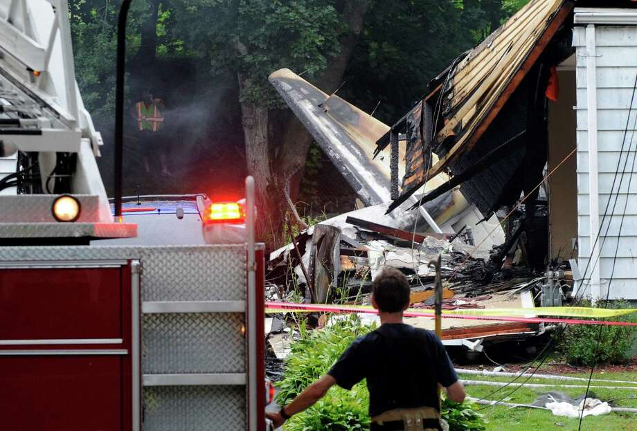 A firefighter surveys the scene of a small plane crash, Friday, Aug. 9, 2013, in East Haven, Conn. The multi-engine, propeller-driven plane plunged into a working-class suburban neighborhood near Tweed New Haven Airport, on Friday. Photo: Fred Beckham, AP Photo/Fred Beckham / Associated Press